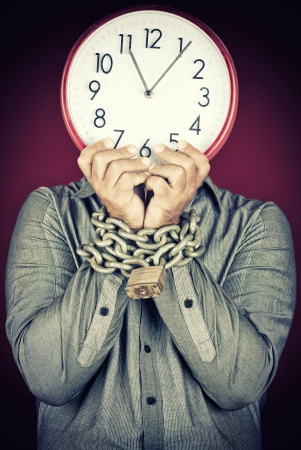 stressed people: Formally dressed man holding a clock in place of his face with his hands chained witha metallic chain and padlock  useful to illustrate overworked  or stressed people  Stock Photo