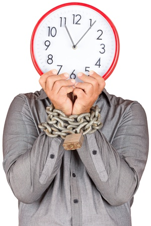 Formally dressed man holding a clock in place of his face with his hands chained witha metallic chain and padlock  useful to illustrate overworked  or stressed people   isolated on white  photo