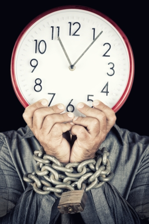 workaholic: Formally dressed man holding a clock in place of his face with his hands chained witha metallic chain and padlock  useful to illustrate overworked  or stressed people   isolated on white