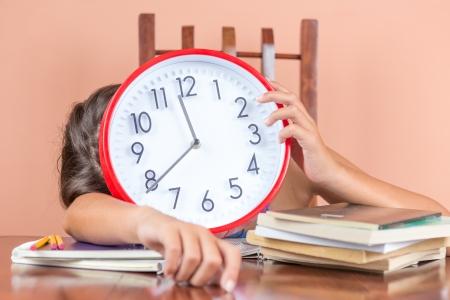 Vermoeide kinderen slapen op een bureau vol boeken en houden van een klok in de plaats van haar gezicht te symboliseren vermoeidheid na te veel studeren