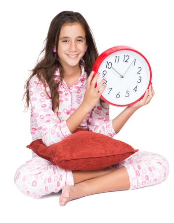 Beautiful hispanic girl wearing pajamas and holding a clock isolated on white photo