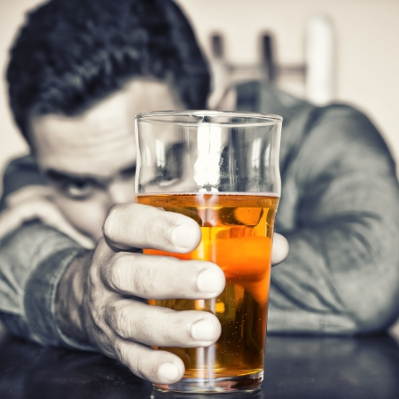 fatigued: Grune image of a drunk man holding a glass of beer Stock Photo