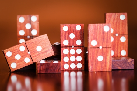dominoes: Tiles from a game of dominoes with reflections on a polished wooden table