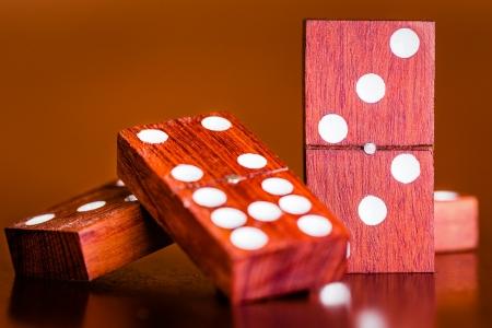 pips: Tegels uit een potje domino op een houten tafel met een diffuus achtergrond