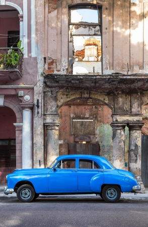 Old car next to crumbling decaying buildings on June 21, 2013 in Havana