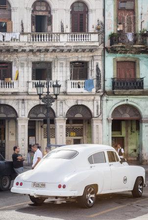 Old american car next to crumbling buildings on June 21, 2013 in Havana Stock Photo - 20449615