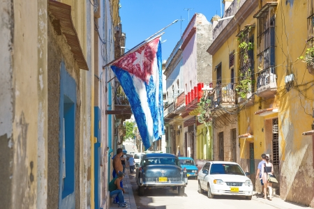 Old colonial buildings with a cuban flag June 28,2013 in Havana With over 2 million inhabitants Havana is the capital of Cuba and the largest city in the Caribbean Stock Photo - 20910040