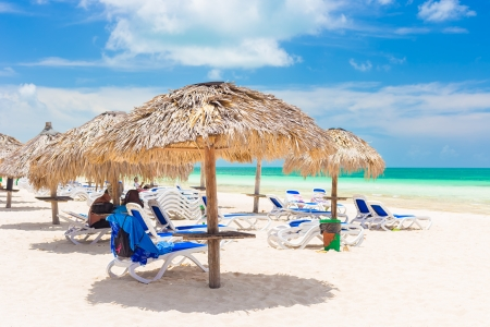 Thatched umbrellas at a resort on the beach of Coco Key  Cayo Coco  in Cuba on a beautiful summer day Stock Photo