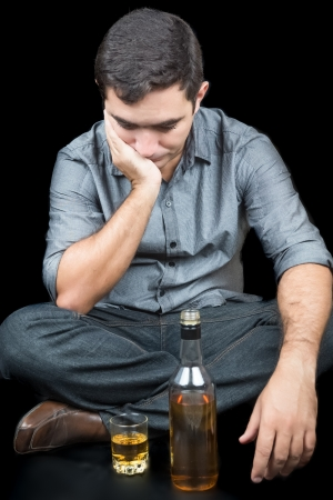 substance abuse: Drunk and lonely man sitting on the floor with a glass and a bottle of liquor  on a black background
