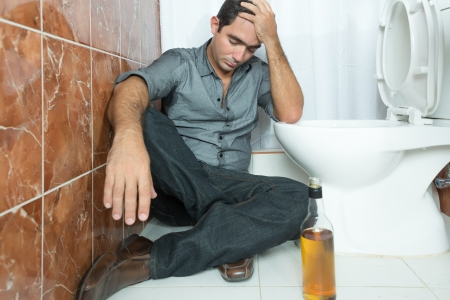 alcoholic man: Drunk and depressed man sitting in the toilet floor with a bottle of liquor