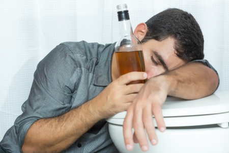 alcohol abuse: Drunk man sleeping on the toilet and holding a liquor bottle