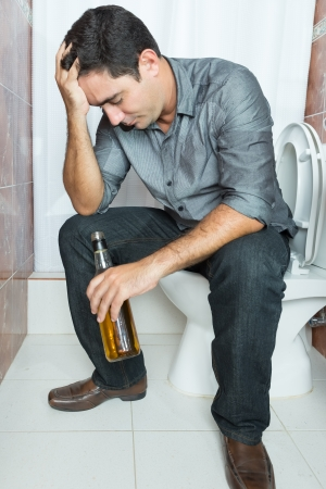 Drunk man with a headache sitting on the toilet and holding a liquor bottle Stock Photo - 21693742