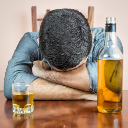 Drunk man sleeping with a whisky bottle and a glass  on his table photo