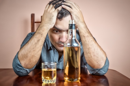 Drunk and depressed hispanic  man suffering a headache  with a liquor bottle on a table