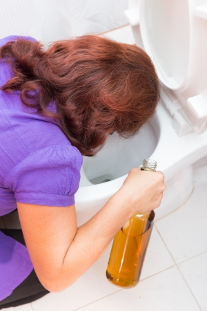 substance abuse: Drunk woman vomiting on a toilet bowl and holding a liquor bottle Stock Photo