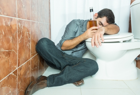dependent: Drunk hispanic man sleeping over the toilet bowl and holding a whisky bottle