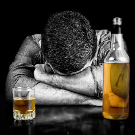 Black and white image of a drunk man sleeping with his head on a table and a bottle of whisky   the bottle and glass have color Stock Photo - 21955240