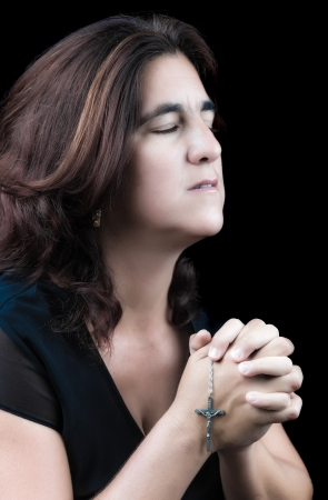 Beautiful hispanic woman praying with her eyes closed and holding a small crucifix  side view, isolated on black  photo