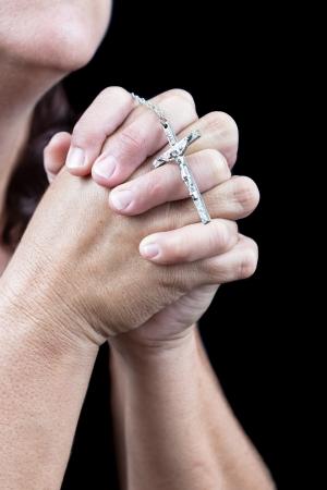 manos orando: Manos orando y sosteniendo un peque�o crucifijo aislado en negro Foto de archivo