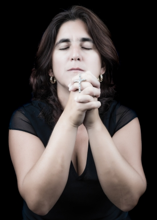 Hispanic woman praying with her eyes closed and holding a small crucifix  isolated on black  photo