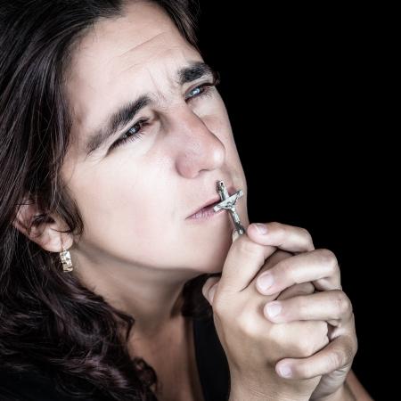 kruzifix: Dramatische Porträt einer hispanische Frau beten und küssen ein Kruzifix isoliert auf schwarz Lizenzfreie Bilder