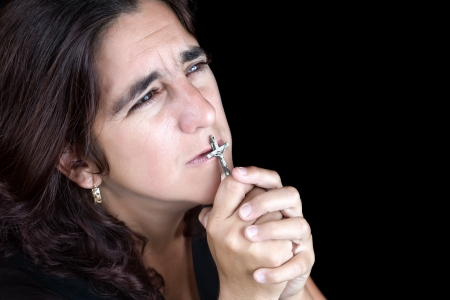 desperate: Desperate and sad hispanic woman praying and kissing a crucifix  isolated on black