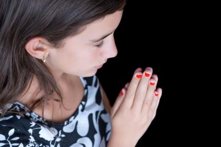 Hispanic girl praying with her eyes closed isolated on a black background photo