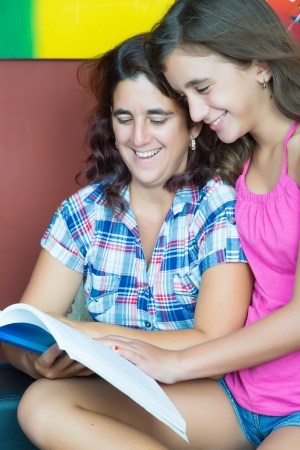 Hispanic mother and her beautiful daughter reading a book at home photo