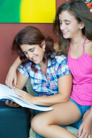 Hispanic mother and her pretty daughter sharing a book at home photo