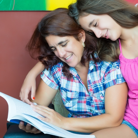 Latin mother and her beautiful teenage daughter reading a book at home Stock Photo
