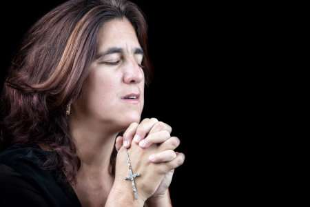Emotional portrait of an hispanic woman praying with a small crucifix  isolated on black  photo