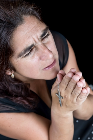 Dramatic portrait of an hispanic woman praying with a small crucifix  isolated on black  photo