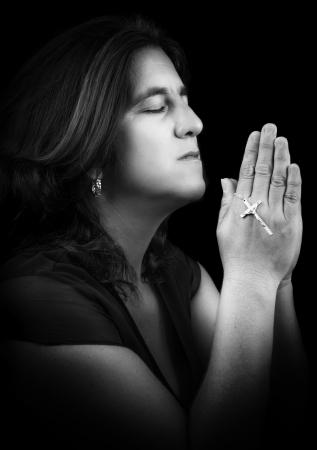 Schwarz-Weiß-Porträt einer hispanische Frau beten und halten eine kleine Kruzifix auf schwarz mit Kopie Raum isoliert Standard-Bild - 22079299