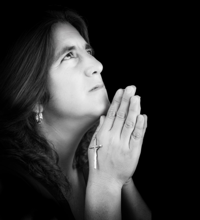 Black and white portrait of a latin woman praying and looking up  isolated on black with copy space  photo
