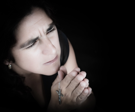 Emotional portrait of a latin woman praying and looking up  isolated on black with copy space  photo