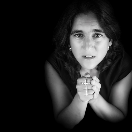 Black and white portrait of an hispanic woman praying and holding a small crucifix  isolated on black with copy space  photo