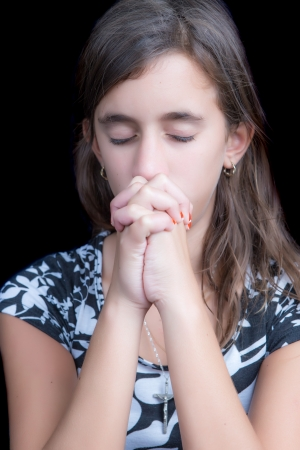 christmas prayer: Cute girl praying with her eyes closed  isolated on back  Stock Photo