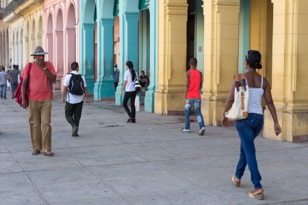Cubans in a street sidelined by colorful buildings in Havana