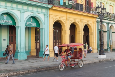 town houses capital: Cuban man with a tricycle waiting for clients  in Havana