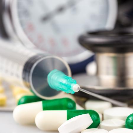 ataque al corazón: Jeringuilla, píldoras diferentes, el estetoscopio y esfigmomanómetro útil para ilustrar cualquier tema médico Foto de archivo