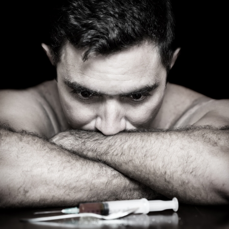 relapse: Grunge image of a depressed drug addict looking at a syringe and drugs