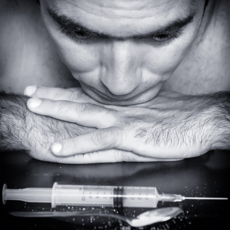 Blue toned portrait of a drug addict contemplating a syringe and drugs with a depressed expression photo