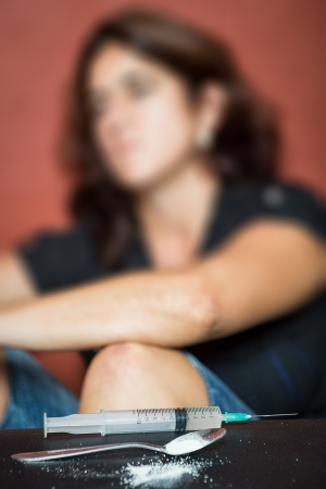 Syringe, drugs and depressed female drug addict sitting in the background photo