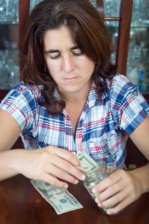 Worried hispanic woman counting her savings at home   useful to illustrate economic problems or difficulty to make ends meet  photo