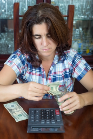 savings problems: Worried hispanic woman counting her savings at home   useful to illustrate economic problems or difficulty to make ends meet