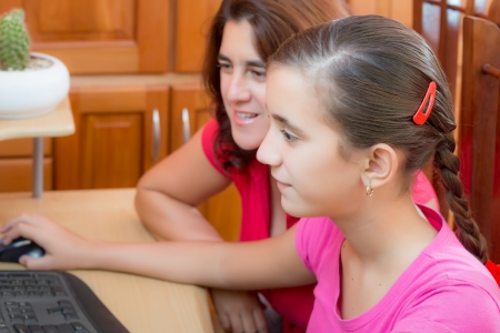 Hispanic girl and her young mother working on a computer or browsing the web photo