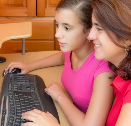 computer game: Young hispanic girl and her beautiful mother working on a desktop computer
