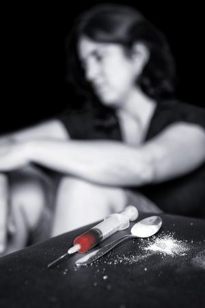 drogadicto: Imagen oscura de un adicto a las drogas y una jeringa