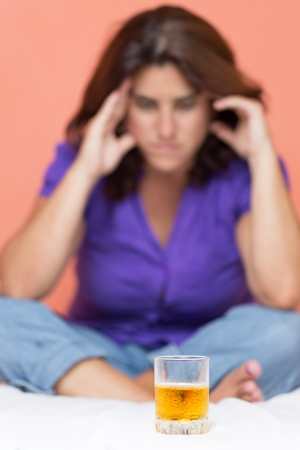 Depressed alcohol addict with a headache looking at a glass of whiskey photo