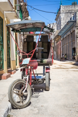 Street scene in Havana with an  old three wheeled bicycle and decaying buildings Stock Photo - 22991315